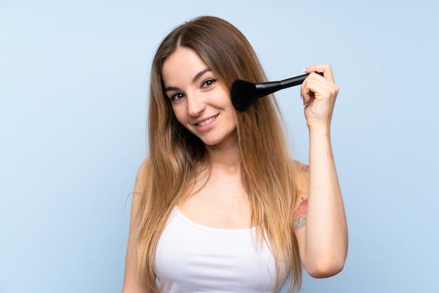 Junge frau über lokalisierter blauer wand mit make-upbürste Premium Fotos