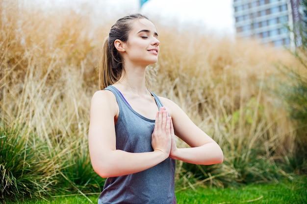 Junge frau übt yoga und meditiert im lotussitz im park Premium Fotos