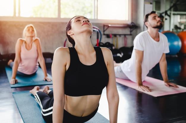 Junge frau und männer, die gesundes körpertraining des lebensstils in der turnhalle, sportart-yogakonzept ausbilden Premium Fotos