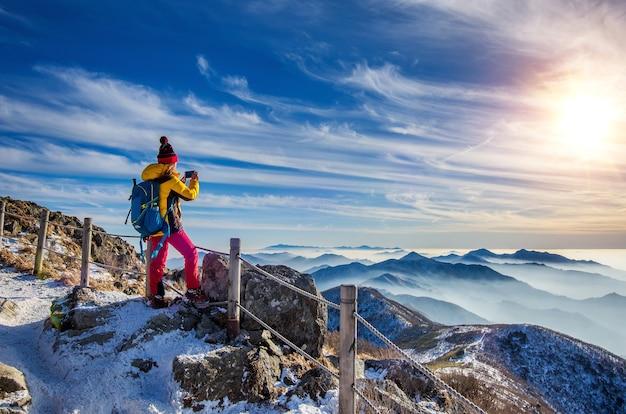 Junge frau wanderer, die foto mit smartphone auf gebirgsspitze im winter nimmt Kostenlose Fotos