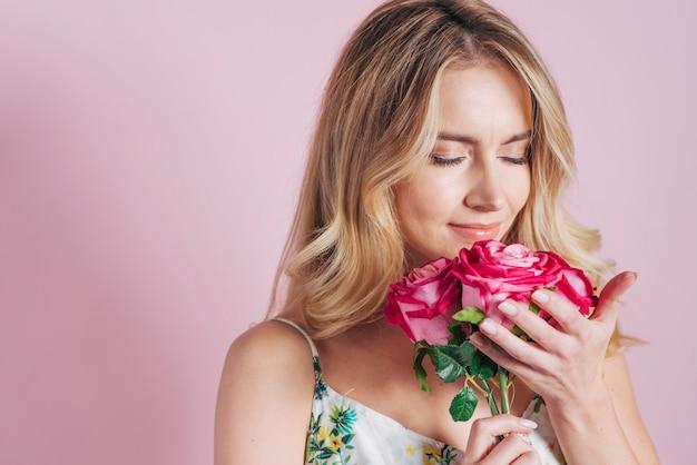 Junge frau, welche die rosen gegen rosa hintergrund riecht Kostenlose Fotos