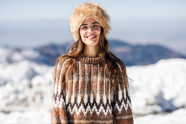 Junge frau, welche die schneebedeckten berge im winter genießt Premium Fotos
