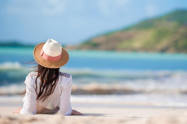 Junge frau, welche die sonne ein sonnenbad nimmt durch perfekten türkisozean genießt Premium Fotos