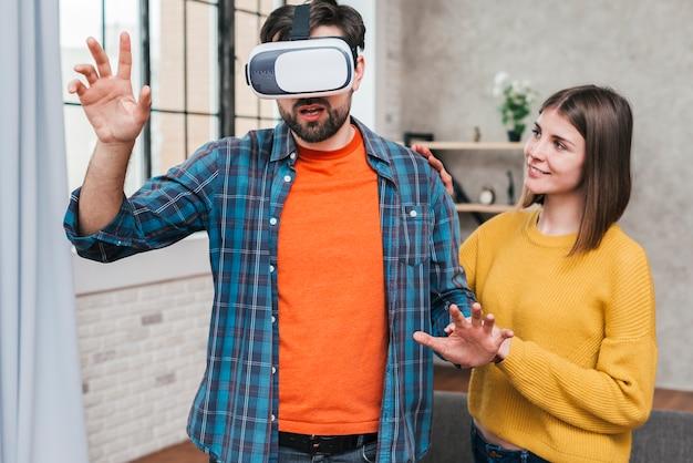 Junge frau, welche die tragende kamera der virtuellen realität des mannes berührt seine hände in einer luft stützt Kostenlose Fotos
