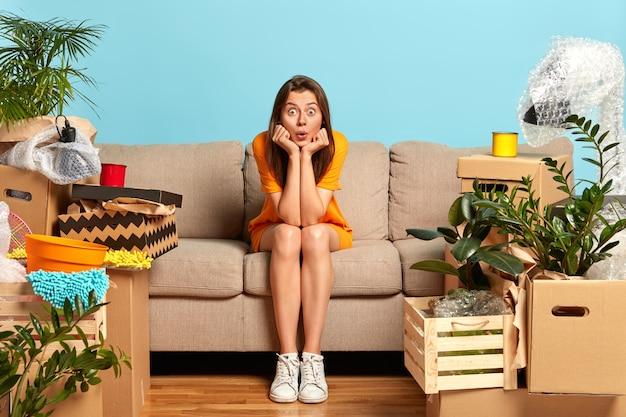 Junge frau zieht in neu gekaufte wohnung, posiert auf der couch mit geschocktem ausdruck Kostenlose Fotos