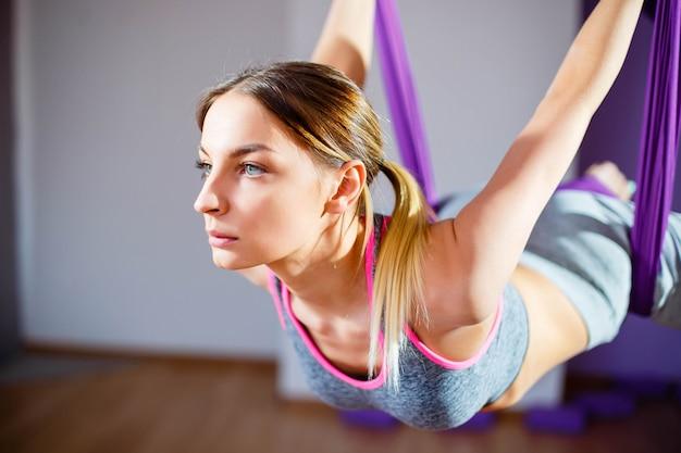 Junge frauen des porträts, die antigravitationsyoga machen. aerial aero fly fitnesstrainer training. harmonie- und gelassenheitskonzept Premium Fotos