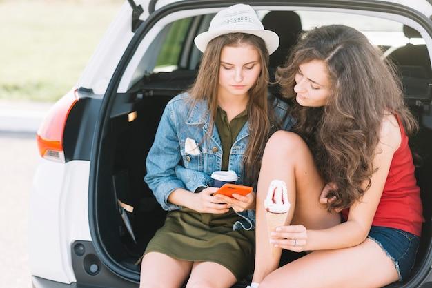 Junge frauen, die auf autokofferraum mit telefon sitzen Kostenlose Fotos