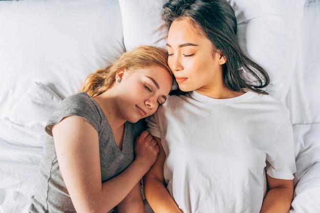 Junge frauen, die das schlafen im bett streicheln Kostenlose Fotos