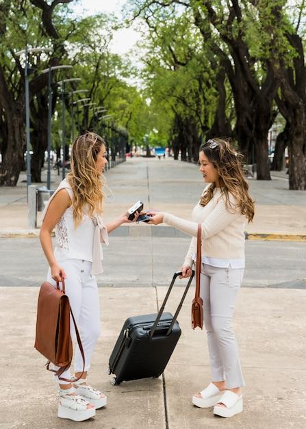 Junge frauen, die den visapass austauschen, der im park steht Kostenlose Fotos