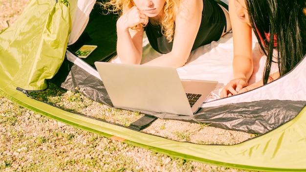 Junge frauen, die laptop im zelt verwenden Kostenlose Fotos