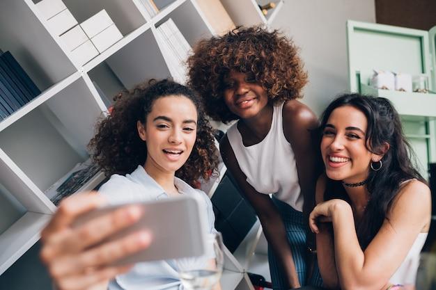 Junge frauen, die selfie mit smartphone nehmen und spaß in der modernen position haben Premium Fotos