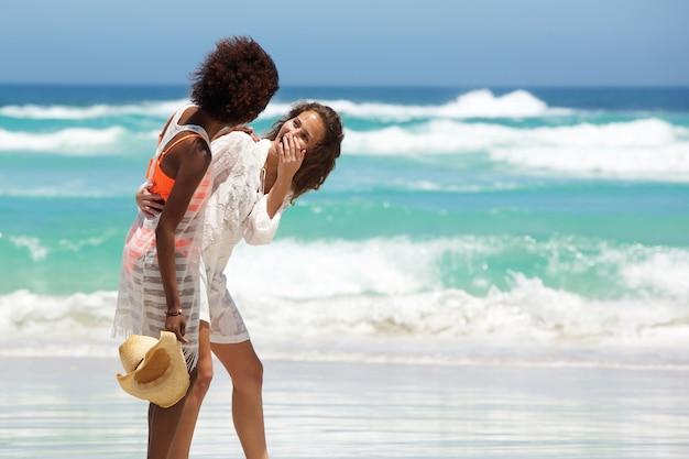 Junge frauen, die über den strand lachen Premium Fotos