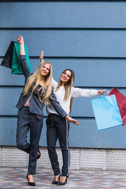 Junge frauen, die vor der wand anheben ihre hände anhalten einkaufstaschen stehen Kostenlose Fotos