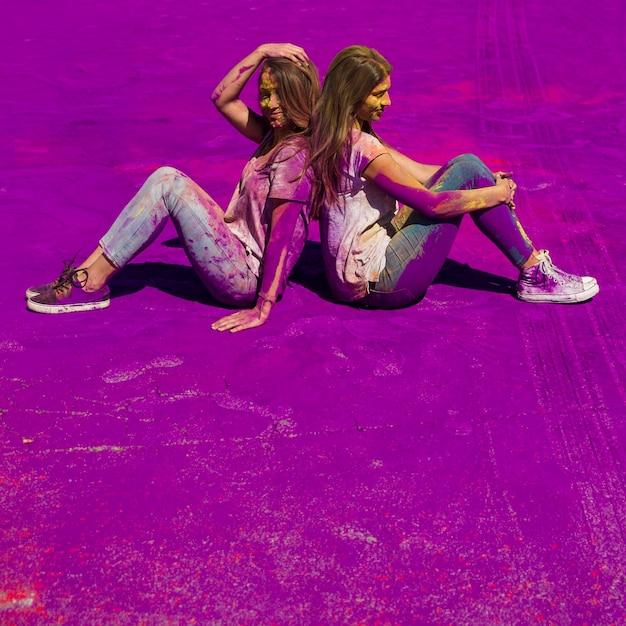 Junge frauen, die zurück zu rückseite über der purpurroten holi farbe sitzen Kostenlose Fotos