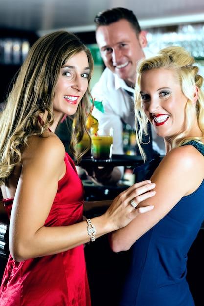 Junge frauen in der bar oder im club, der barkeeper serviert cocktails Premium Fotos