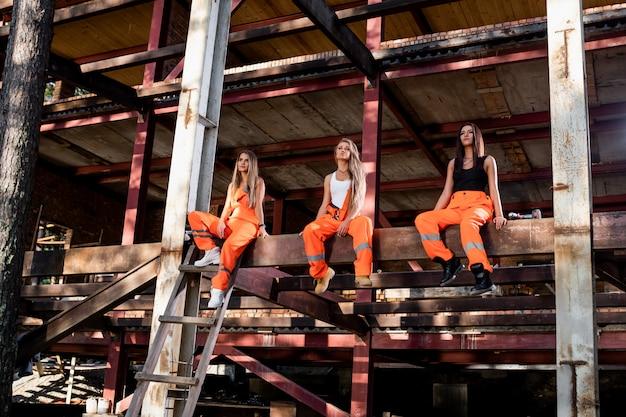 Junge frauen in einer orangefarbenen uniform sitzen in einem unfertigen gebäude. baumeisterinnen. weibliche arbeit. häuser bauen. Premium Fotos