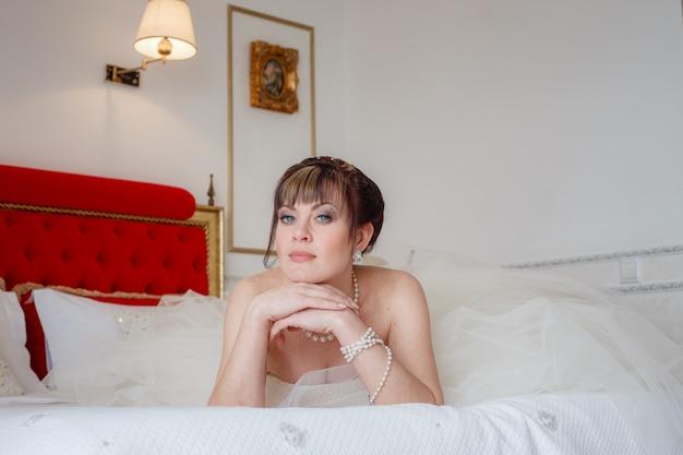 Junge frauen mit hochzeitskleid im sehr hellen raum Premium Fotos