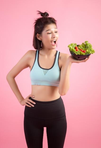 Junge frauen mögen gemüse auf einem rosa essen. Kostenlose Fotos