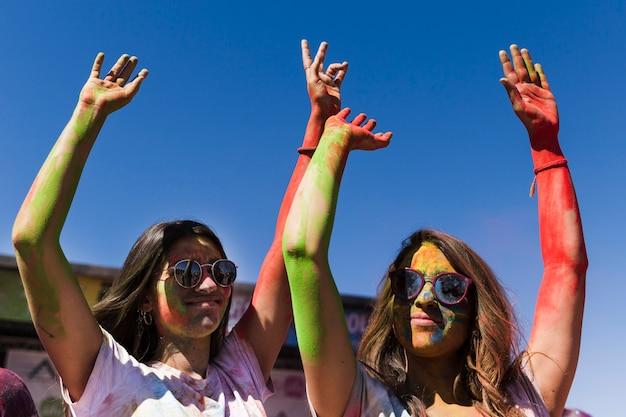 Junge frauen, welche die sonnenbrille genießt das holi festival gegen blauen himmel tragen Kostenlose Fotos