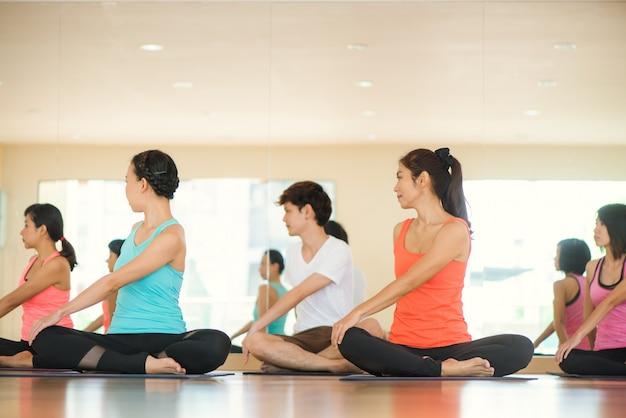 Junge frauen yoga drinnen bleiben ruhig und meditiert beim üben yoga, um den inneren frieden zu erforschen. yoga und meditation haben gute vorteile für die gesundheit. foto-konzept für yoga sport und gesunde lebensweise Kostenlose Fotos