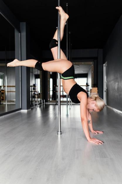 Junge frauleistung auf pole dance Kostenlose Fotos