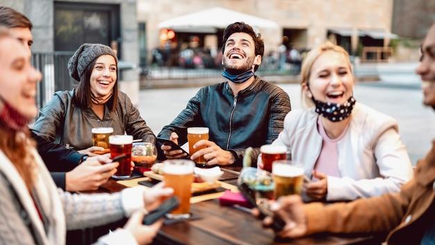 Junge freunde, die bier tragen gesichtsmaske trinken Premium Fotos