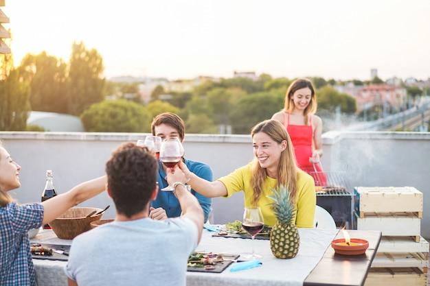 Junge freunde, die grillparty bei sonnenuntergang auf penthouse-terrasse haben Premium Fotos