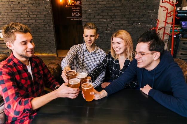 Junge freunde, die mit gläsern bier in der bar rösten und klirren Kostenlose Fotos
