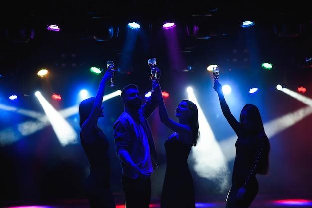 Junge freunde, die mit gläsern champagner in den händen tanzen. Premium Fotos