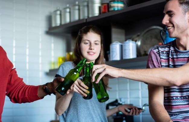 Junge freunde, die spaß mit flaschen zu hause haben. Premium Fotos
