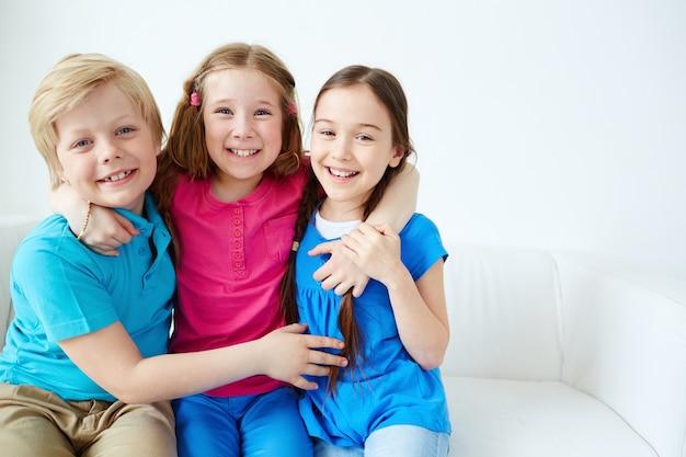 Junge freunde umarmte auf dem sofa Kostenlose Fotos