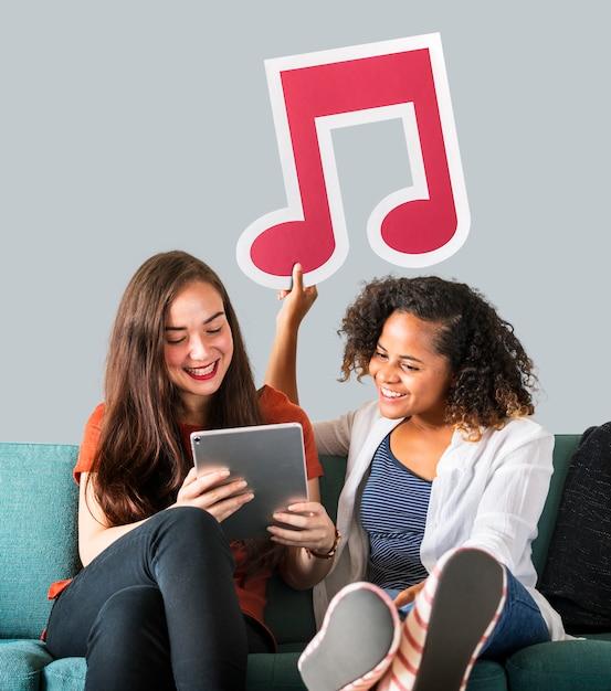 Junge freundinnen, die eine ikone der musikalischen anmerkung halten Kostenlose Fotos