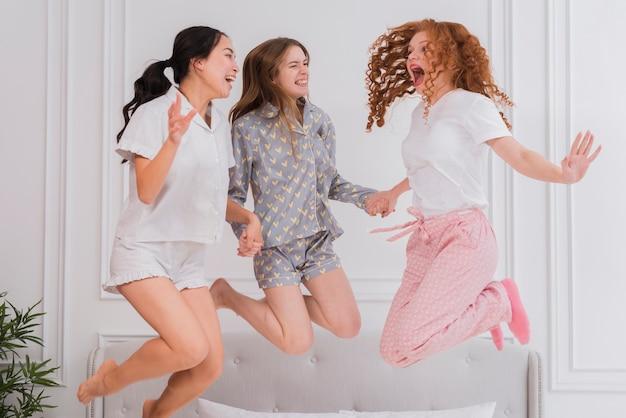 Junge freundinnen, die in bett springen Kostenlose Fotos