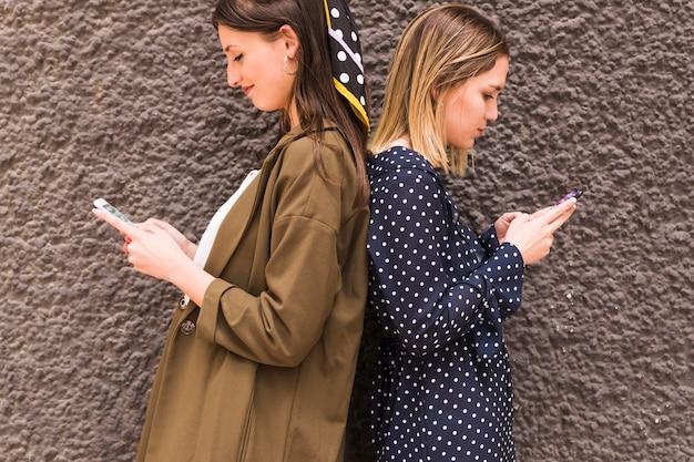 Junge freundinnen, die zurück zu rückseite unter verwendung des handys stehen Kostenlose Fotos