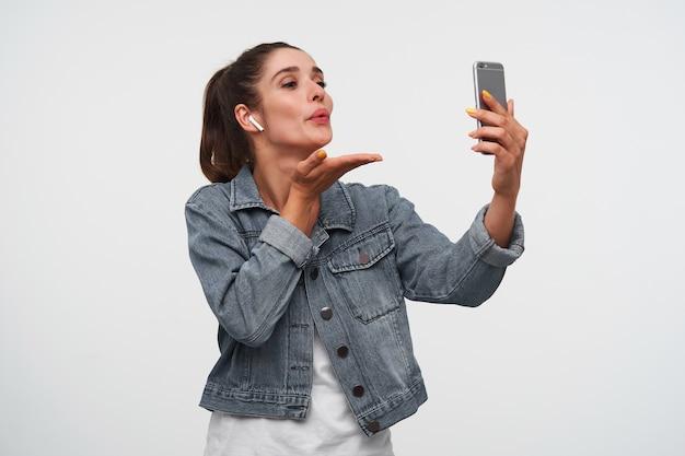 Junge fröhliche brünette dame trägt in weißem t-shirt und jeansjacken, hält smartphone und schickt kuss an den videochat. steht über weißem hintergrund. Kostenlose Fotos