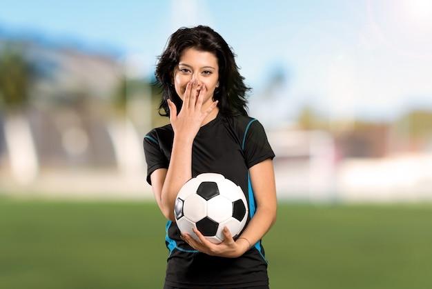 Junge fußballspielerfrau mit überraschungsgesichtsausdruck an draußen Premium Fotos