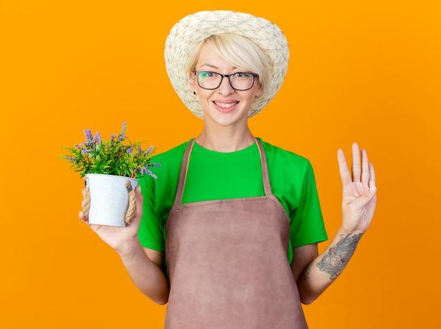 Junge gärtnerfrau mit den kurzen haaren in der schürze und im hut, die topfpflanze betrachten, die kamera lächelnd mit glücklichem gesicht zeigt, das nummer vier über orange hintergrund steht Kostenlose Fotos
