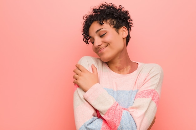 Junge gemischte afroamerikanerjugendlichfrau umarmt und lächelt sorglos und glücklich. Premium Fotos