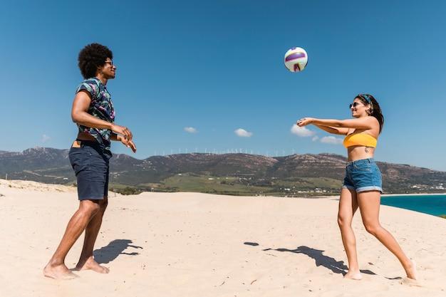 Junge gemischtrassige paare, die spiel mit ball auf strand spielen Kostenlose Fotos