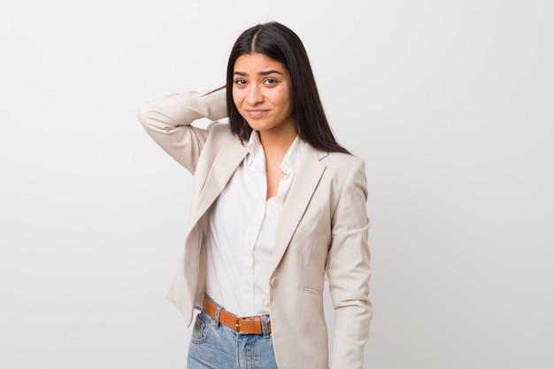 Junge geschäftsaraberfrau lokalisiert gegen einen weißen hintergrund, der zurück vom kopf berührt, eine wahl denkt und trifft. Premium Fotos