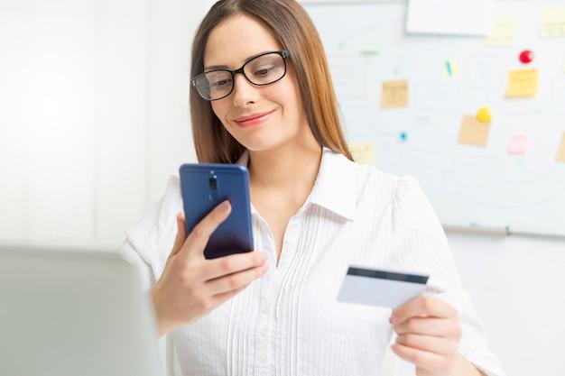 Junge geschäftsfrau benutzt einen handy und eine kreditkarte für online-zahlung. Premium Fotos