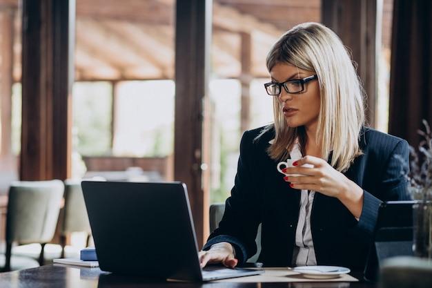 Junge geschäftsfrau, die am computer in einem café arbeitet Kostenlose Fotos