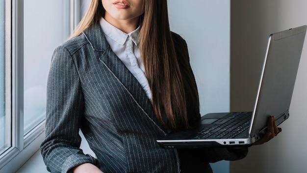 Junge geschäftsfrau, die am fenster mit laptop steht Kostenlose Fotos