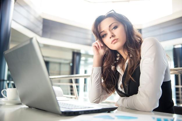 Junge geschäftsfrau, die am laptop arbeitet. Premium Fotos