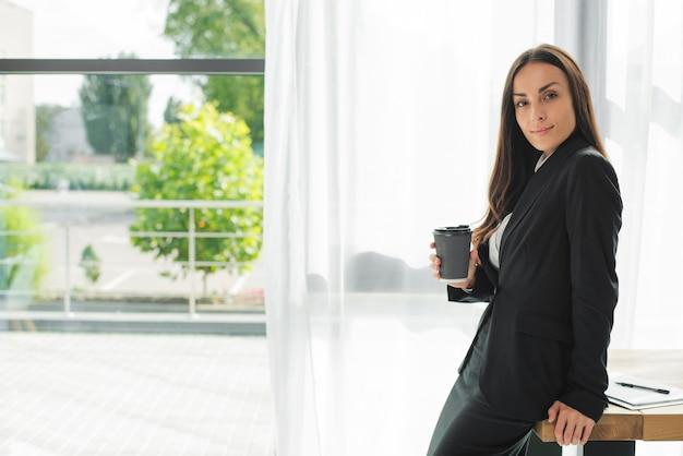 Junge geschäftsfrau, die am rand des hölzernen schreibtisches hält wegwerfkaffeetasse nahe dem fenster sitzt Kostenlose Fotos