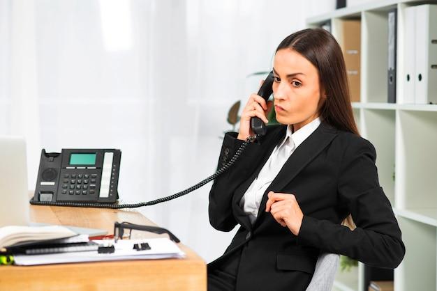 Junge geschäftsfrau, die am telefon sitzt nahe dem schreibtisch spricht Kostenlose Fotos
