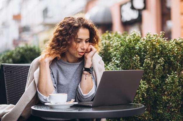 Junge geschäftsfrau, die an einem computer außerhalb des cafés arbeitet Kostenlose Fotos