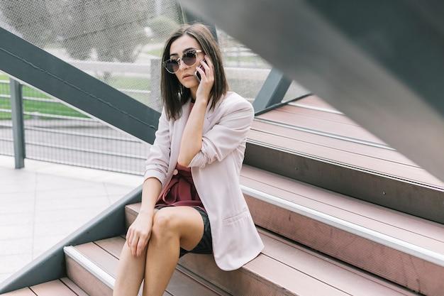 Junge geschäftsfrau, die auf dem treppenhaus spricht auf smartphone sitzt Kostenlose Fotos