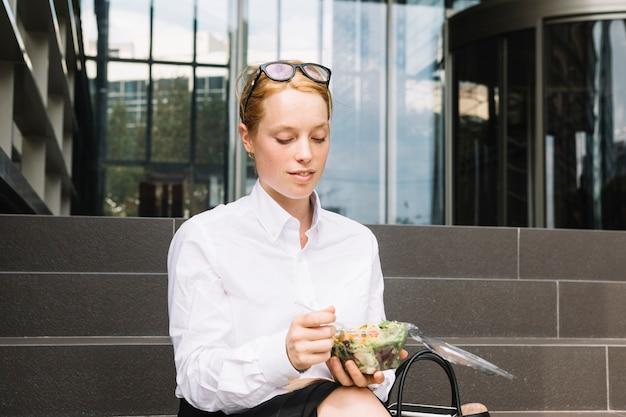 Junge geschäftsfrau, die außerhalb des büros isst brotdose sitzt Kostenlose Fotos