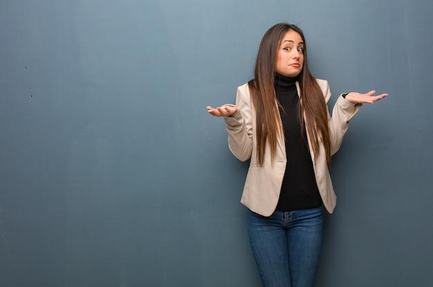 Junge geschäftsfrau, die schultern zweifelt und zuckt Premium Fotos